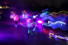 Athletes dressed in glow sticks and body paint run past.