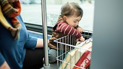 A child chooses a book from the KDL Books on the Bus program rack.