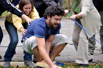 Christina Keller helps steady Nick Monoyios as they complete a team building challenge.