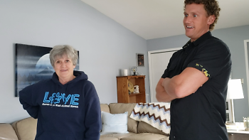 Barb and Mark smile while standing in a living room together.