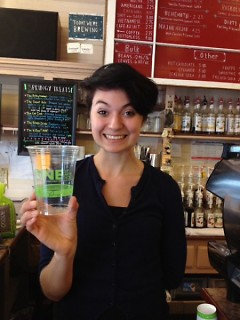 Amanda Ebenhoeh of The Sparrows Coffee Tea & Newsstand displaying their compostable cups.