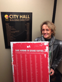 Erica Curry VanEe stands with her petition of over 1,000 signatures against the Airbnb regulations.