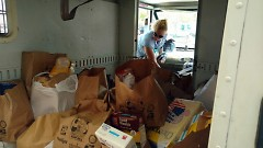 A letter carrier unloads donations from her postal vehicle, Saturday, May 13.