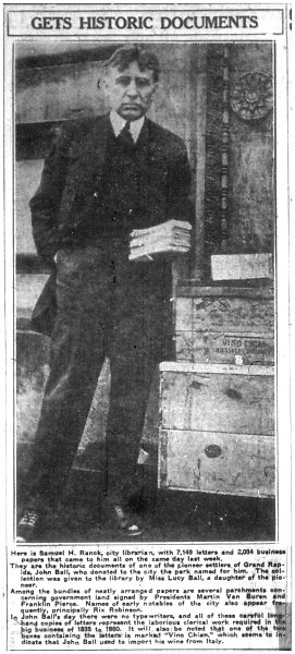 Samuel Ranck, first director of the Grand Rapids Public Library, holds a box of letters written by early pioneer John Ball