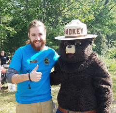 Young State Park Explorer Guide Devin Burke poses with Smokey the Bear during Free Fishing Weekend, June 11-12, 2016.