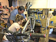Lead Mechanic Morgan Barkley works with a neighbor on his bike at The Spoke Folks