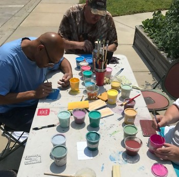Dwelling Place residents enjoy an outdoor painting activity to beautify their community garden downtown.