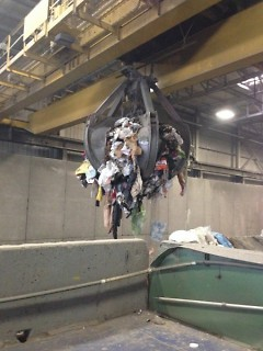 """Covanta's crane, the """"claw"""", loading garbage at the incinerator"""