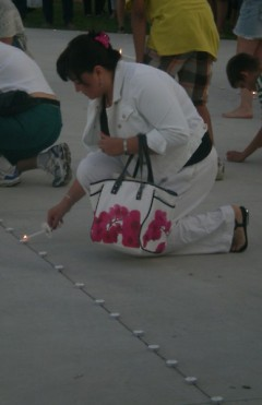 A woman lights one of over 200 candles laid out during the vigil to pay her respects
