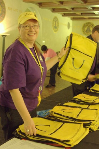 Volunteer Ann Videtich from Kalamazooon shows off one of the LaughFest bags for purchase.