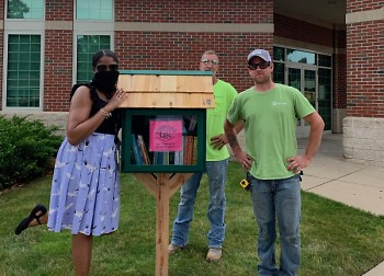 Zandra Blake, GRPL Seymour Branch Manager, and Rockford Construction crew admiring new Storytime Grand Rapids Book Pantry.